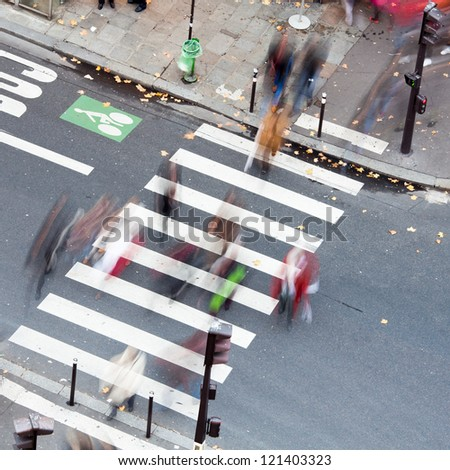 people crossing the city street on the zebra crossing
