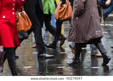 people crossing the street on a rainy day