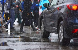 People crowd on a pedestrian crosswalk with a stopped car. Wet weather in city.