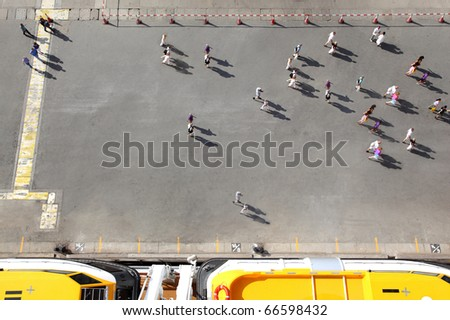 People crowd one-way movement on the wharf near yellow boats on cruise ship