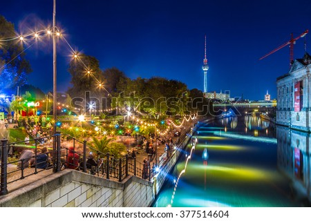 People dancing at summer Strandbar beach party near Spree river at historic Museum Island with famous TV tower in the background in twilight during blue hour at dusk, Berlin Mitte district, Germany