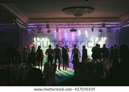 People dancing in the neon lights during the wedding party - Shutterstock ID 427030339
