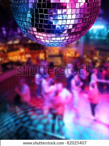 People dancing under colorful lights of disco mirror ball