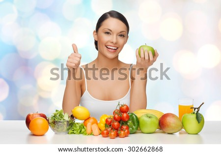 people, diet, gesture and vegetarian concept- happy asian woman with healthy food showing thumbs up over blue lights background