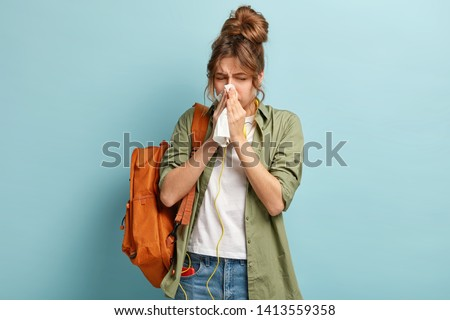People, disease concept. Ill dark haired woman sneezes in handkerchief, carries rucksack, listens music in headphones, dressed casually, stands against blue background. Student feels unwell.