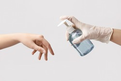 People disinfecting hands on light background