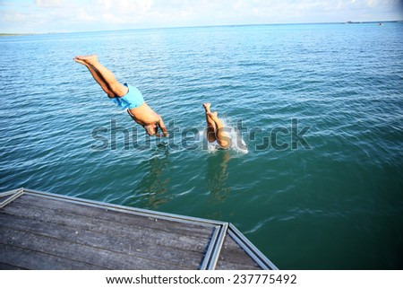 People diving from pontoon into water
