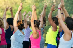 people doing exercise in a park at sunset, with hands up
