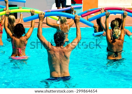 people doing water aerobics in a pool of a resort