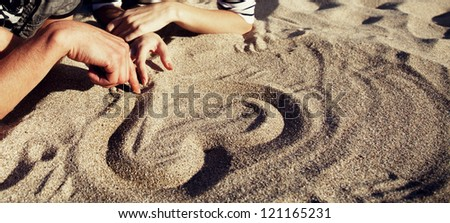 People drawing heart at sand.