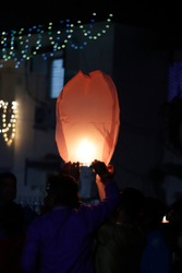 People dressed in traditional dresses lightning red or orange sky lantern during Deepawali - the Hindu festival of light, prosperity, and victory of good over the evil.