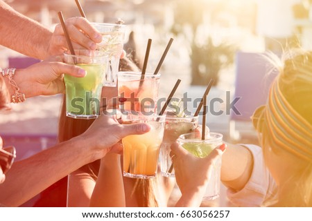 people drinking at party outdoor. group of friends cocktails in hand toasting with glasses.close up on hands and drinks