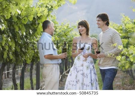 People drinking wine in vineyard