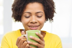 people, drinks and leisure concept - happy african american woman drinking tea from cup or mug at home