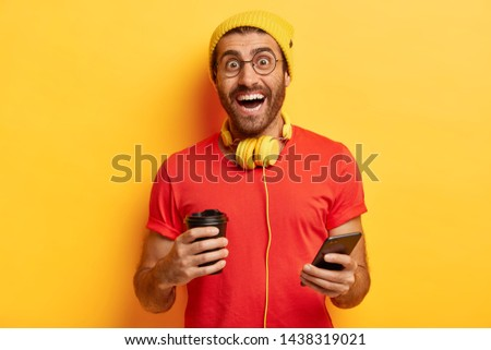 People, drinks, leisure and technology concept. Cheerful millennial guy stands with coffee cup and smartphone, has glad expression, wears red t shirt and yellow headgear, chats with friends.