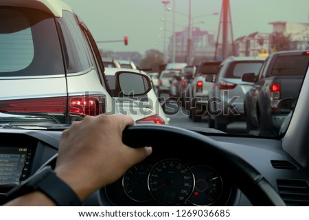 People driving inside car and many cars on the road jam in traffic junction by red light control, Rush hour in Thailand on day.