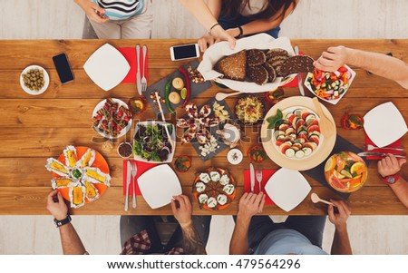 People eat healthy meals at festive table served for party. Friends celebrate with organic food on wooden table top view. Happy company having lunch #479564296