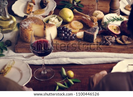 People eating a platter of cheese with seasonal fruits and wine #1100446526