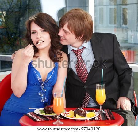 People eating cake in restaurant. Loving couple.