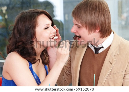 People eating cake in restaurant. Loving couple.