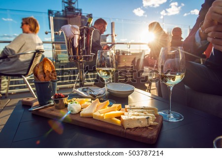 People eating cheese and drinking wine at rooftop restaurant at sunset time. Restaurant table served with cheese plate, bread and white vine full of visitors.