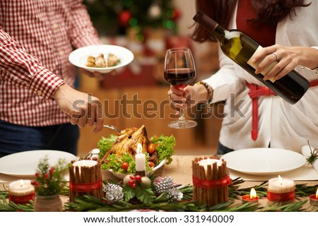 People eating roasted chicken and drinking red wine at Christmas dinner