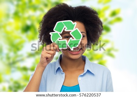 people, ecology, conservation and recycling concept - happy african american young woman looking through recycle symbol over green natural background