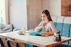 People, education, job and freelance concept. Stylish young female freelancer or student girl sitting at table at cafe, having coffee, waiting for friend or client, open copybook in front of her