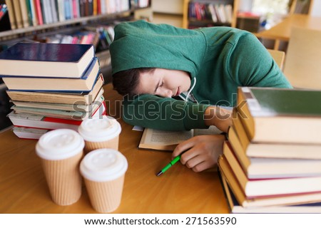people, education, session, exams and school concept - tired student or young man with books and coffee sleeping in library