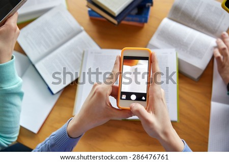 people, education, technology and exam concept - close up of students with smartphones taking picture of books page and making cheat sheet in school library