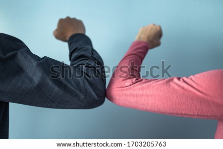 People elbow bump greeting each other.  Alternative for hand shake to help stop the spread of germs, coronavirus concept.