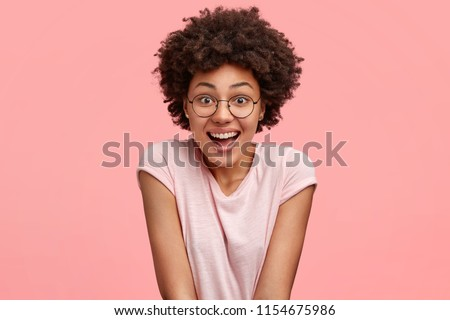 People, emotions and pleasant feelings concept. Beautiful young African American female with joyful expression, smiles happily as watches funny programme during spare time, wears casual t shirt #1154675986