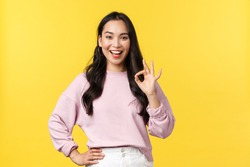 People emotions, lifestyle and fashion concept. Impressed and excited smiling asian woman totally agree with you, showing okay sign and nod approval, standing yellow background
