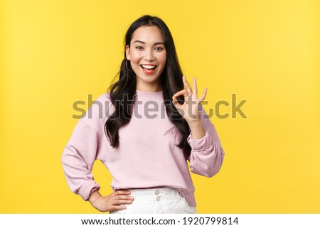 People emotions, lifestyle and fashion concept. Impressed and excited smiling asian woman totally agree with you, showing okay sign and nod approval, standing yellow background Stock photo ©