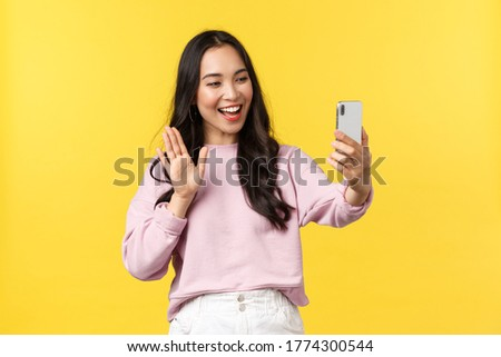 People emotions, lifestyle leisure and beauty concept. Cute outgoing asian girl talking on videocall with friends, waving hand to say hi at phone camera, blogger have live stream, yellow background