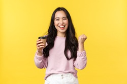 People emotions, lifestyle leisure and beauty concept. Enthusiastic and energized smiling asian woman drinking cup of tasty coffee from best cafe takeaway, fist pump happy, got pumped up