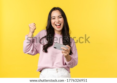 People emotions, lifestyle leisure and beauty concept. Enthusiastic asian girl gamer playing mobile phone, tilting smartphone to pass level in game, smiling amused, fist pump as winning, chanting yes