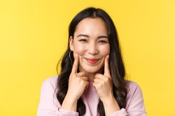 People emotions, lifestyle leisure and beauty concept. Happy pretty young asian woman pointing at her cute dimples and smiling broadly, advertising face care products or makeup, yellow background