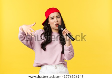 People emotions, lifestyle leisure and beauty concept. Stylish and cool young girl rapper in red cap, singing song and gesturing, performing with microphone, standing yellow background Stock fotó ©