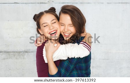 people, emotions, teens and friendship concept - happy smiling pretty teenage girls hugging and laughing over gray concrete wall background