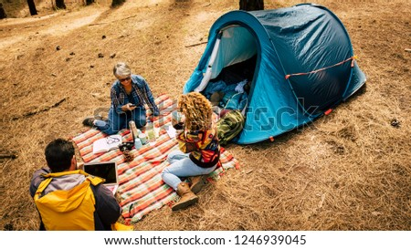 People enjoy free camping in the pines forest using technology laptop and mobile phoner and relaxed from the stress society - outdoor lifestyle for alternative traveler - top view