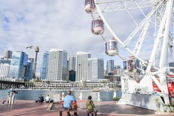 People enjoy sitting at the Darling Harbour with part of Ferris Wheel