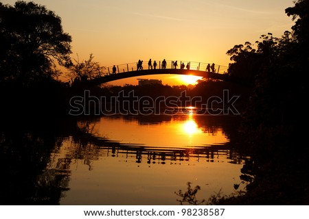 People enjoy sunset on bridge in Park Ibirapuera Sao Paulo Brazil. - stock photo