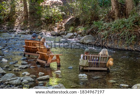 People enjoy the afternoon sitting in wooden chairs placed in the Big Sur River, in California.  Stockfoto ©