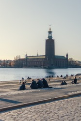 people enjoy the spring weather and the view from Riddarholmen towards Stockholm City Hall. The famous city hall is the venue for the Nobel Prize banquet.
