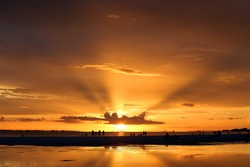 People enjoying a  dramatic sunset over Sanibel Island as seen from For Myers Beach, Florida, USA