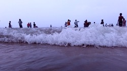People enjoying, clicking photos with splashing water wave in the water at Puri sea beach in India