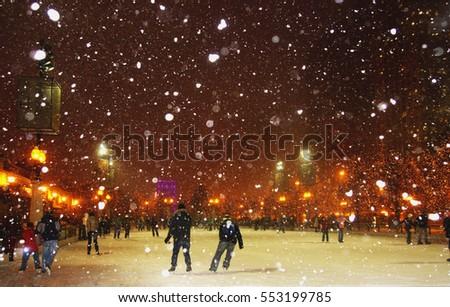 People enjoying ice skating during snowy night in Chicago.