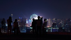 People enjoying new year firework on a skyscraper rooftop. Bangkok Thailand, New year eve 2016