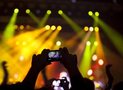 People enjoying rock concert and taking photos with cell phone at music festival
